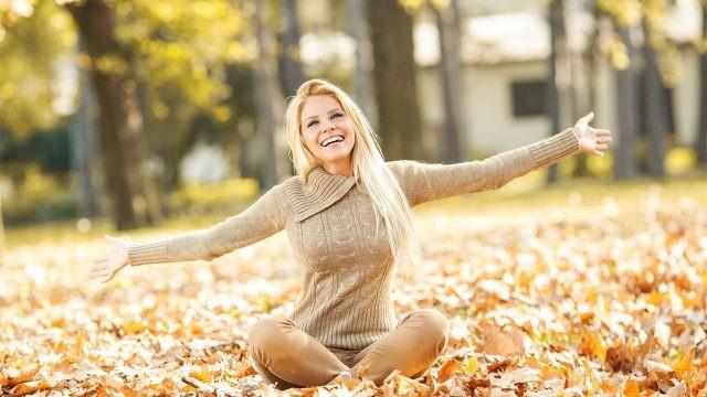 Девушка в позе лотоса в осеннем парке