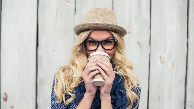 Девушка в шляпе и очках пьёт кофе