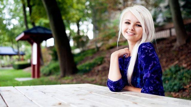 Девушка в синей блузке за столом в парке