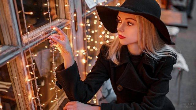 Фотомодель в чёрном пальто и шляпе у окна с гирляндой