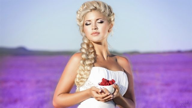 Красивая блондинка с малиной в ладошках