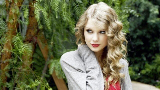 Кудрявая блондинка на фоне зелени