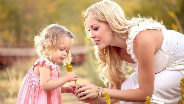 Мама с дочкой рассматривают цветы