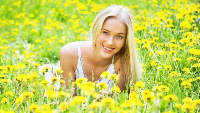 Милая девушка в поле одуванчиков