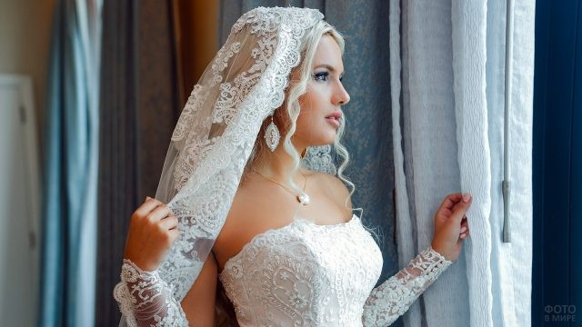 Невеста в ажурной фате смотрит в окно