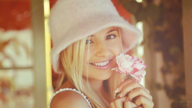 Нежная девушка в пушистой шляпке держит цветок