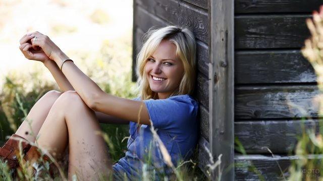 Радостная девушка в траве возле сарая
