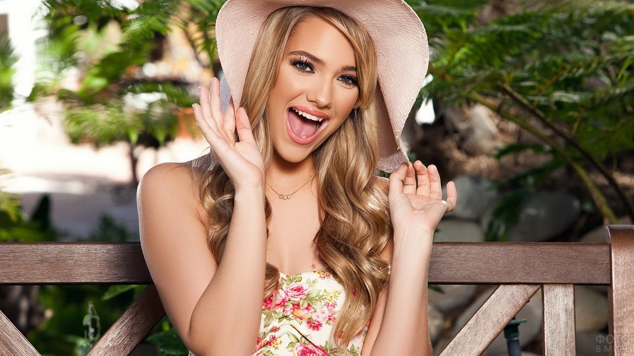 Весёлая блондинка в шляпе на скамейке