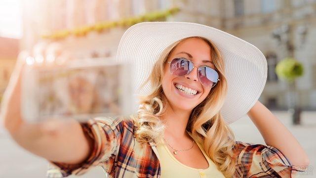 Весёлая девушка в шляпе делает селфи