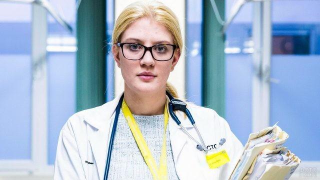 Врач в очках в коридоре больницы