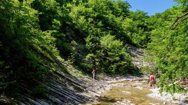 Туристы по руслу реки пробираются к Плесецким водопадам