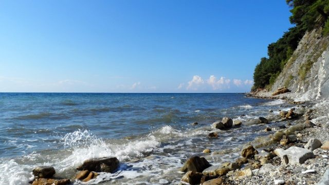Волна разбивается о камни на диком пляже