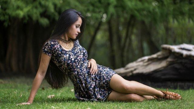 Брюнетка сидит на газоне
