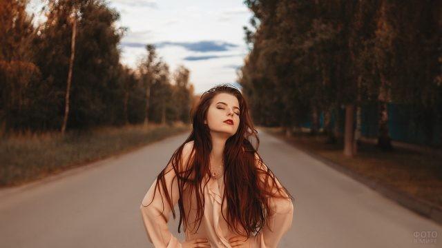 Девушка стоит посреди дороги с закрытыми глазами