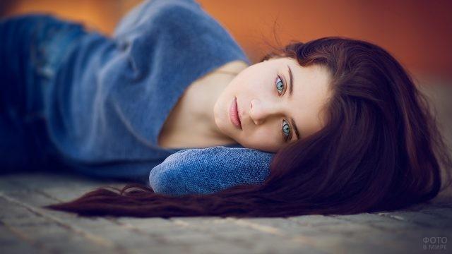 Голубоглазая брюнетка лежит на полу
