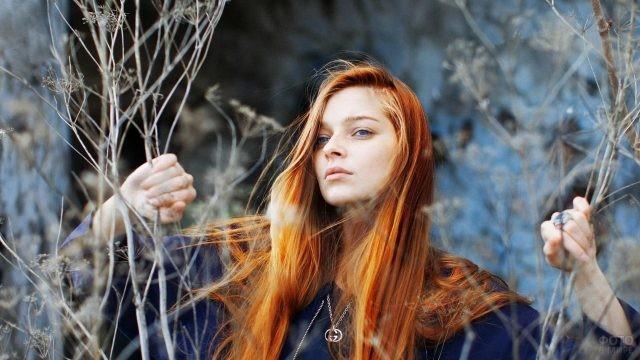 Рыжеволосая девушка держится за сухие ветки