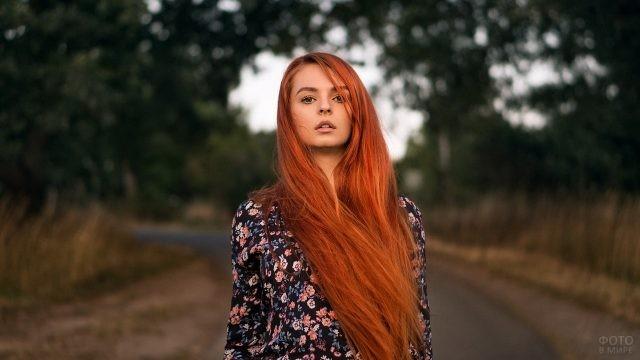 Рыжеволосая девушка стоит посреди дороги