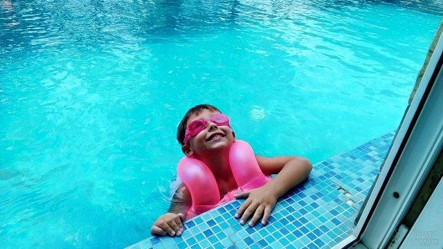 Счастливый мальчик в бассейне у окна
