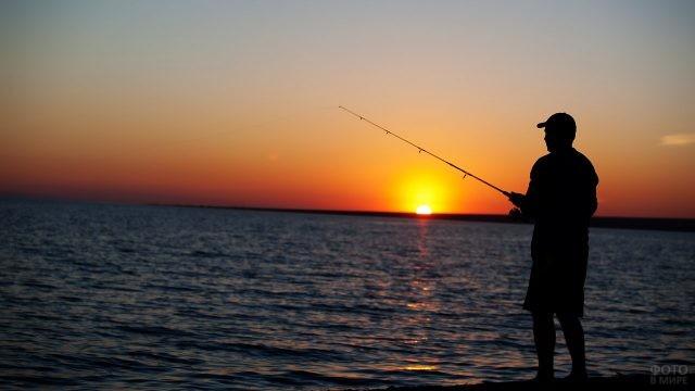 Силуэт рыбака на фоне заката над морем