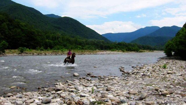 Турист на лошади форсирует реку