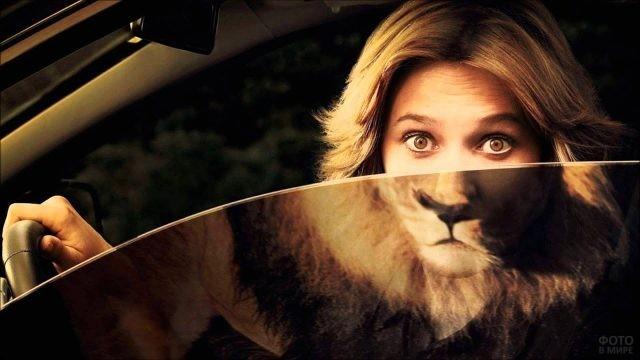 Блондинка выглядывает из машины с отражением льва