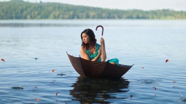 Брюнетка сидит в зонте на воде