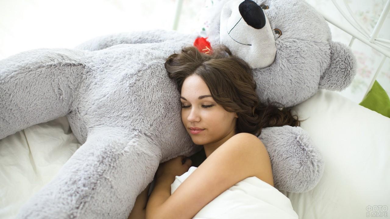 Брюнетка спит на большом медведе