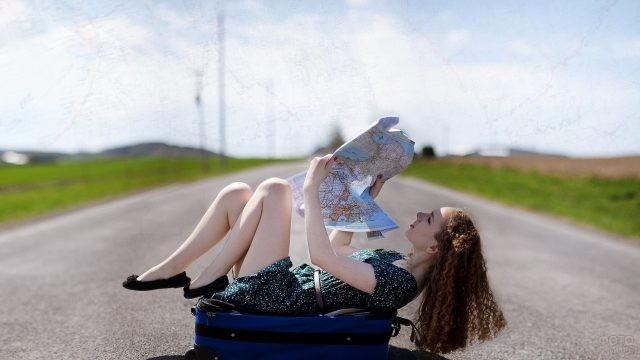 Девушка изучает карту, лёжа на чемодане