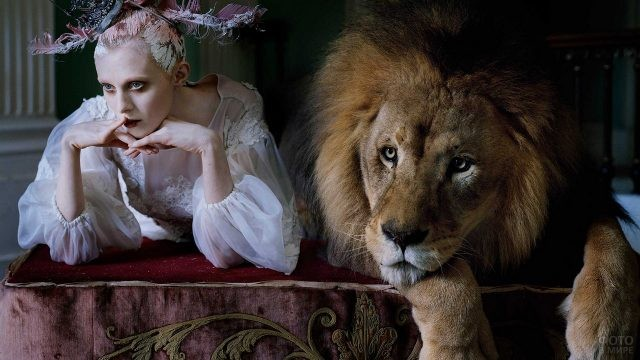 Нарядная девушка сидит рядом со львом