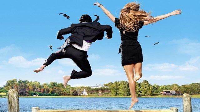 Парень с девушкой прыгают в воду, разбросав вещи