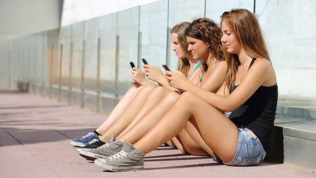 Три девушки сидят в одинаковых позах с телефонами