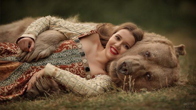 Весёлая девушка лежит в обнимку с медведем