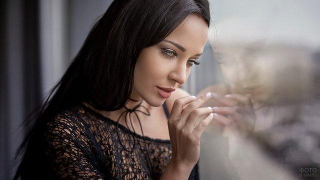 Брюнетка смотрит в окно