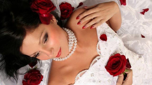 Невеста в жемчужных бусах среди роз