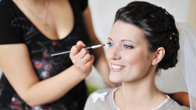 Визажист наносит свадебный макияж