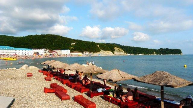 Тропические зонтики над красными шезлонгами на пляже