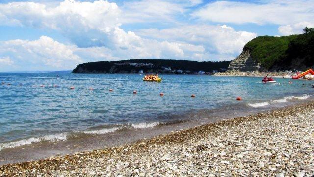 Туристы подплывают на надувном банане к пляжу