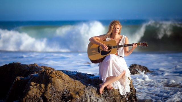 Блондинка с гитарой на фоне прибоя