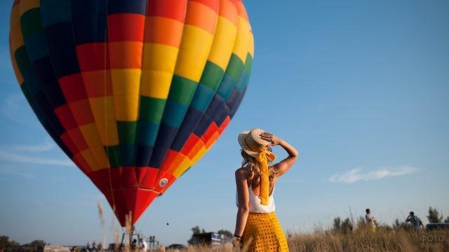 Блондинка в шляпе смотрит на воздушный шар