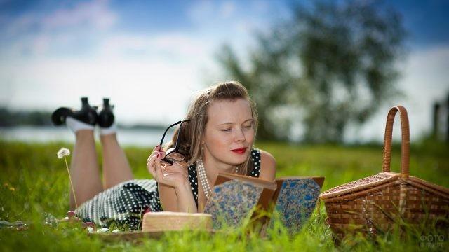Девушка читает книгу на полянке