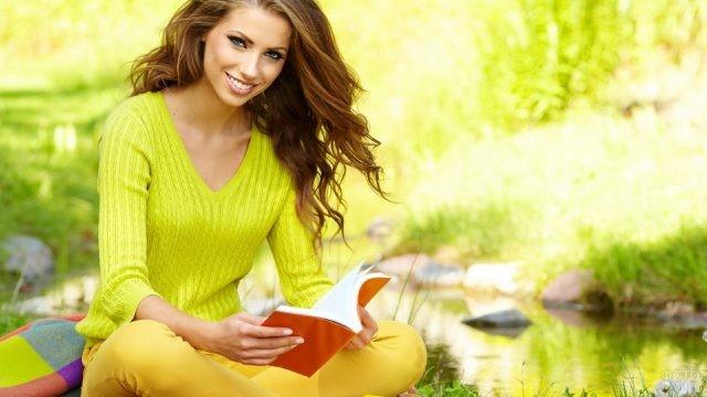 Девушка читает книгу у озера