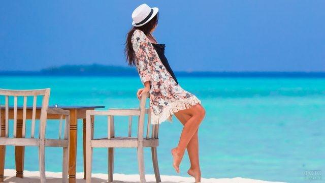 Девушка облокотилась на стул на пляже