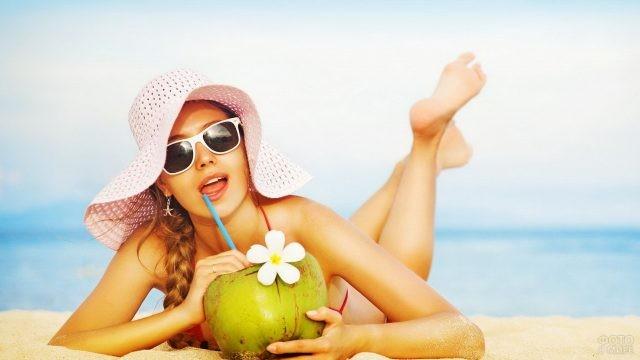 Девушка пьёт из фрукта на пляже