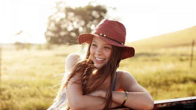 Девушка в бордовой шляпе смеётся