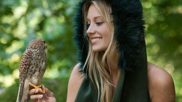 Девушка в капюшоне держит сокола