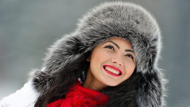 Девушка в меховой шапке улыбается