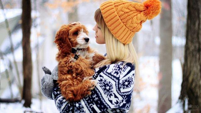 Девушка в рыжей шапке с собакой зимой