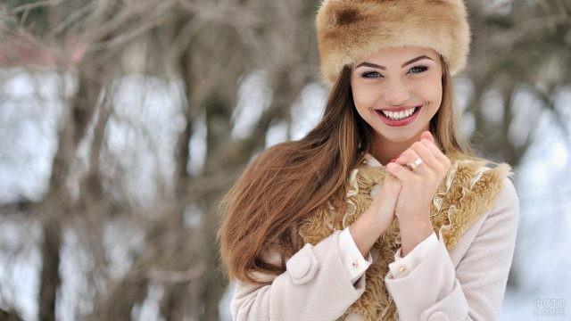 Девушка в светлой меховой шапке в лесу