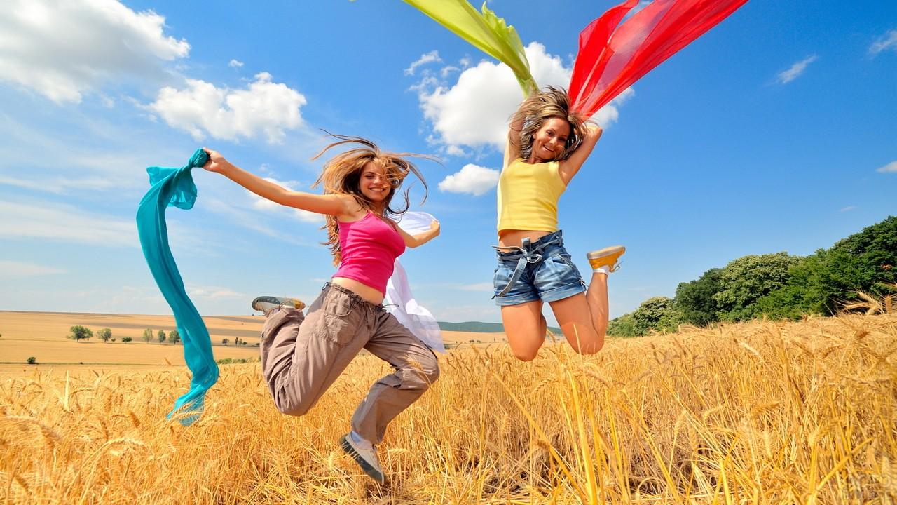 Девушки с цветными шарфами в прыжке