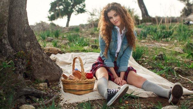 Кудрявая девушка в кедах на пикнике